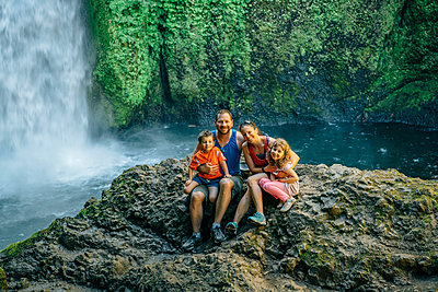 Portrait of happy family sitting on rocks against waterfall at forest - p1166m1547038 by Cavan Images