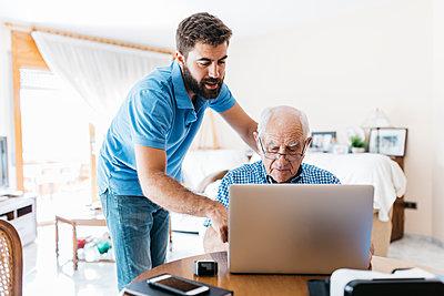 Adult grandson teaching his grandfather to use laptop - p300m2023802 by Josep Rovirosa