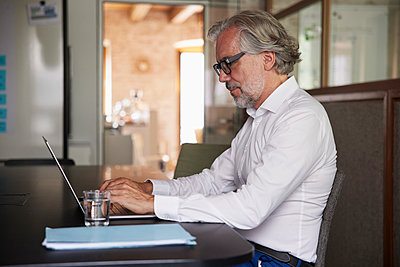 Mature businessman working on laptop at desk in office - p300m2299945 by Rainer Berg