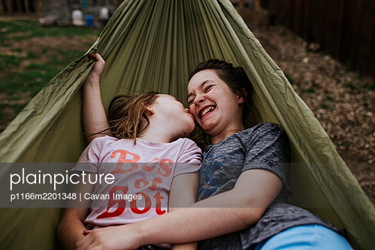 young girls goofing around in hammock outside - p1166m2201348 by Cavan Images