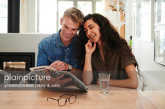 Paar betrachtet ein Magazin - p1640m2254666 von Holly & John