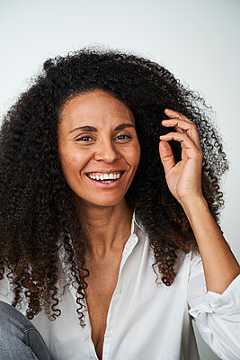 Happy woman with hand in hair over gray background - p300m2264580 by Annika List