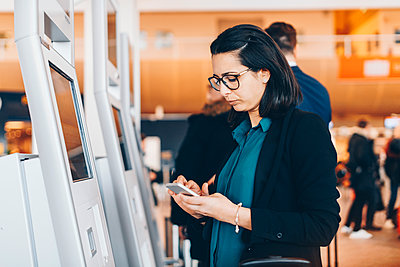 Businesswoman using mobile phone by automated check-in machine in airport - p426m1580062 by Maskot
