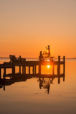 Silhouette of Caucasian children on wooden dock - p555m1453271 by Mark Edward Atkinson/Tracey Lee