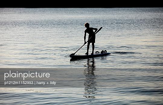 Junge paddelt mit dem Surfbrett - p1212m1152993 von harry + lidy
