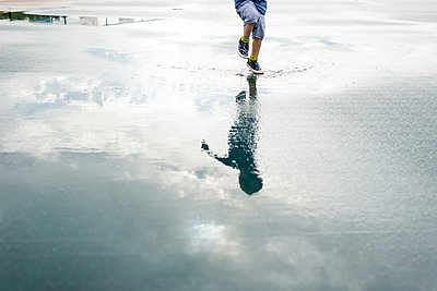 Reflection of boy jumping in puddle - p1166m1186134 by Cavan Images