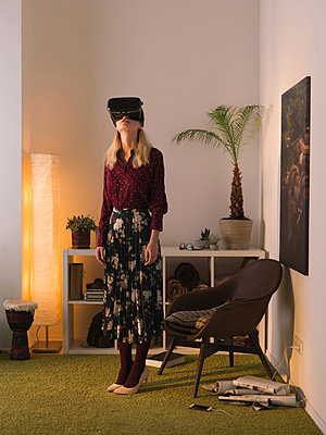 Full length of woman using virtual reality simulator while standing against wall at home - p1166m1542062 by Cavan Social