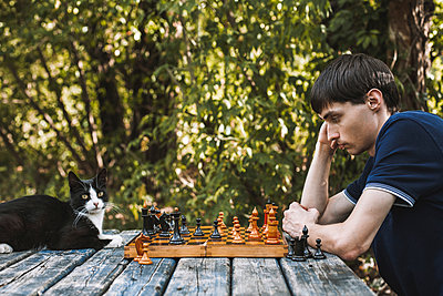 Side view of serious man looking at chess pieces by cat on wooden table at backyard - p1166m1546253 by Cavan Social