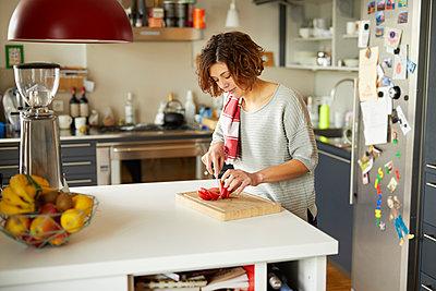 Mature woman cutting tomato in kitchen - p300m1587091 von Philipp Nemenz