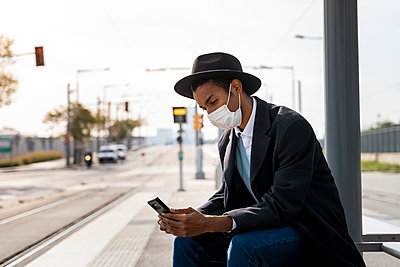 Young man using mobile phone at bus stop during COVID-19 - p300m2239951 by VITTA GALLERY