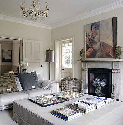 Coffee table books and modern artwork above fireplace in living room of Guildford home - p349m790394 by Brent Darby