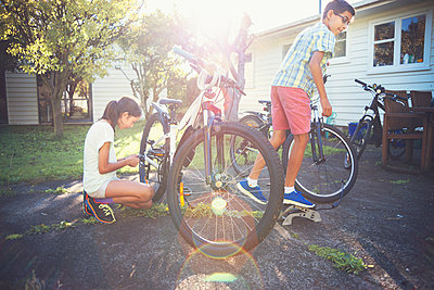 Mixed race children fixing bicycles in backyard - p555m1411867 by Donald Iain Smith