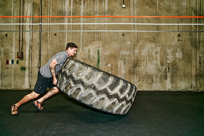 Caucasian man lifting large tire in gym - p555m1459447 by Peathegee Inc