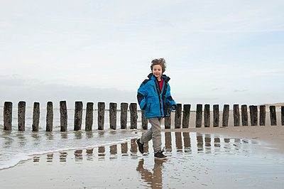 Boy walking on beach - p896m835037 by Sabine Joosten