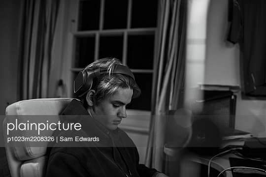 Teenage boy with headphones at desk in bedroom - p1023m2208326 by Sam Edwards