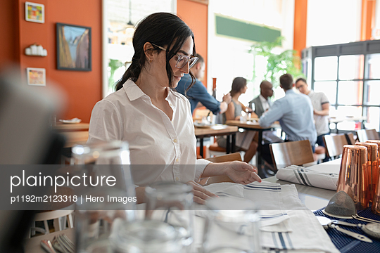 Waitress folding napkins in restaurant - p1192m2123318 by Hero Images