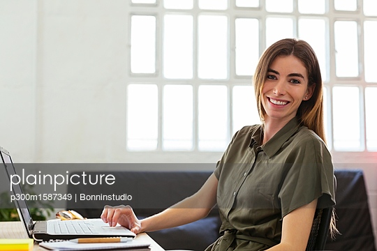 Portrait of smiling young woman with laptop at desk in office - p300m1587349 von Bonninstudio