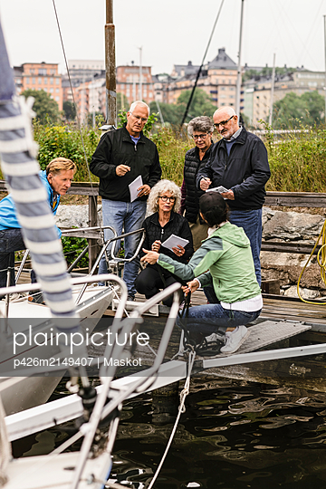 Senior men and women listening to female instructor by yacht during boat master course - p426m2149407 by Maskot