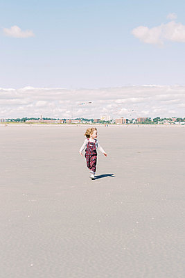 A little girl running on a big beach with her hand flying in the wind - p1166m2212920 by Cavan Images