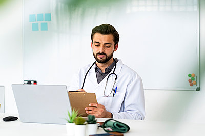 Male healthcare worker with clipboard and laptop sitting at desk - p300m2275465 by Giorgio Fochesato