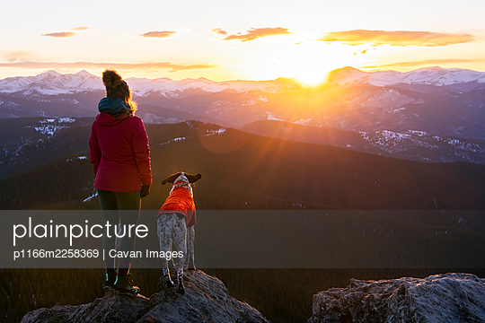Woman with dog looking at landscape from mountain peak during sunset - p1166m2258369 by Cavan Images