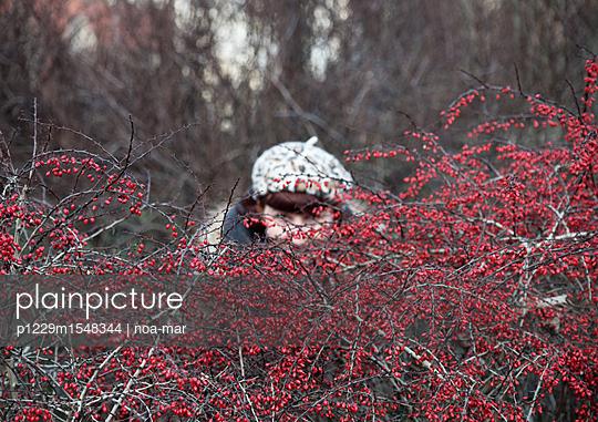 Frau versteckt sich hinter Gestrüpp - p1229m1548344 von noa-mar