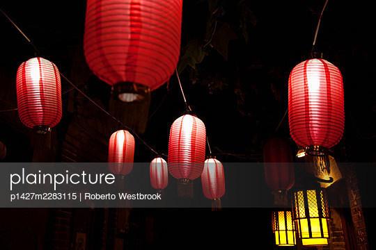 Paper lanterns on city street at night - p1427m2283115 by Roberto Westbrook