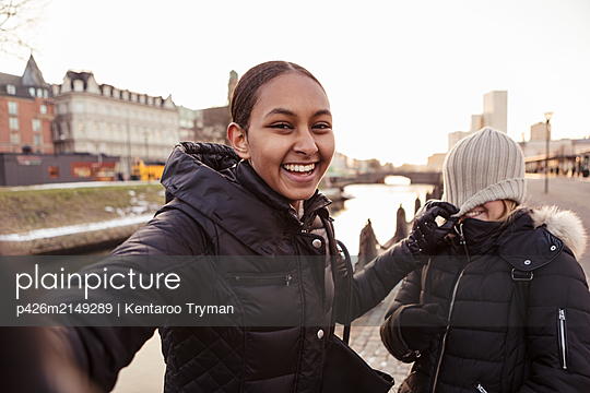 Portrait of happy teenage girl playing mischief with friend in city - p426m2149289 by Kentaroo Tryman
