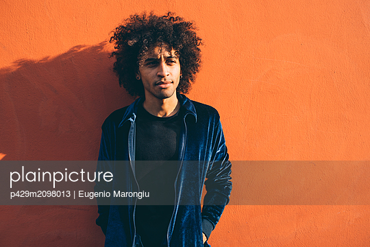Portrait of young man against orange coloured wall - p429m2098013 by Eugenio Marongiu