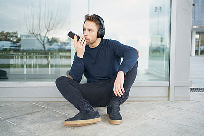 Young man with headphones on city street - p1166m2171507 by Cavan Images