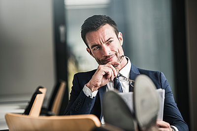 Businessman reading documents, thinking - p300m2059426 by Uwe Umstätter
