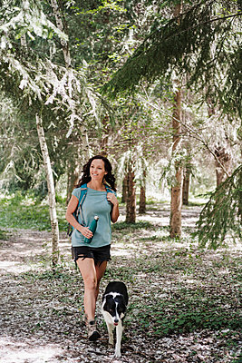 Woman hiking with Border Collie in forest - p300m2293419 by Eva Blanco