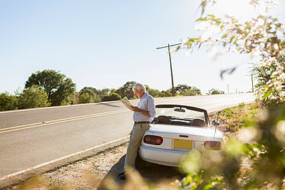 Senior Caucasian man reading map by road - p555m1463836 by Marc Romanelli