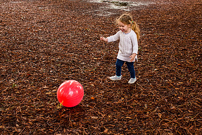 Caucasian girl playing with red ball in autumn - p555m1482046 by Adam Hester