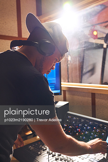 Male music producer at sound board in recording studio - p1023m2190280 by Trevor Adeline