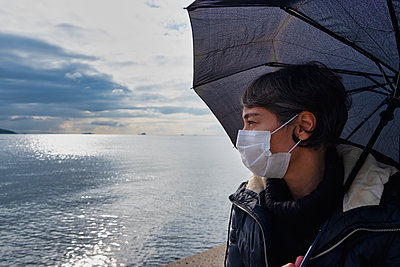 Woman looking at the sea wearing a mask - p1166m2232503 by Cavan Images