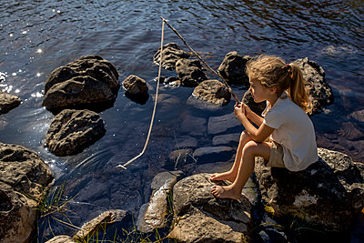 Girl fishing on the lakefront - p1355m1574069 by Tomasrodriguez