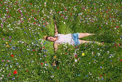 Junge Frau in einer Blumenwiese II - p427m917317 von R. Mohr