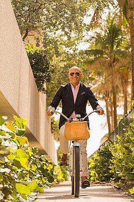 Caucasian businessman riding bicycle - p555m1305586 by Mark Edward Atkinson