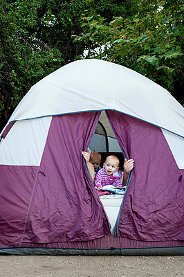 Toddler twins and father peeking out of tent - p924m825971f by Jade Brookbank