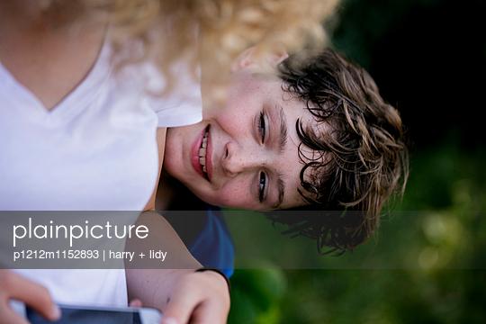 Mädchen schaut auf Smartphone, Junge schaut hervor - p1212m1152893 von harry + lidy