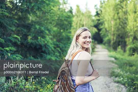 Portrait of smiling young woman with backpack on forest track - p300m2166311 by Bernd Friedel