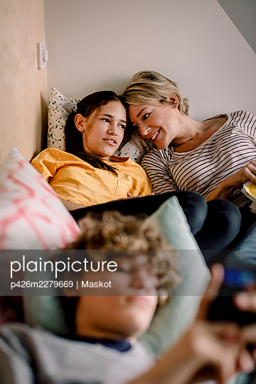 Smiling mother looking at daughter while lying on bed at home - p426m2279669 by Maskot
