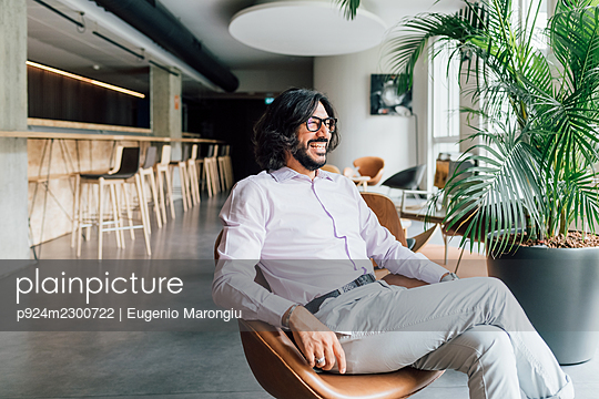 Italy, Smiling man sitting in armchair in creative studio - p924m2300722 by Eugenio Marongiu