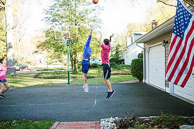 Senior man playing basketball with grandson at backyard - p1166m1210099 by Cavan Images