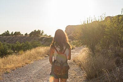 Young woman walks through a dirt road in a meadow. Back view - p1166m2129535 by Cavan Images