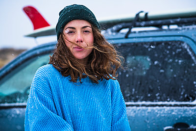 Woman surfer with frozen surfboard - p1166m2177058 by Cavan Images