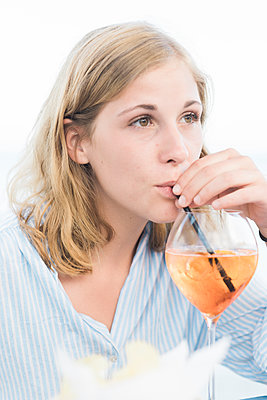 Junge Frau trinkt einen Cocktail - p1437m2008203 von Achim Bunz