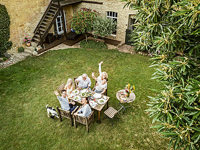 Family eating together in the garden in summer - p300m2103687 von Peter Scholl