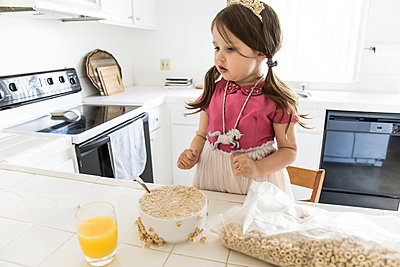 Caucasian girl eating cereal in kitchen - p555m1311490 by Andie Mills